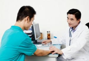 Male doctor checking a patient's pulse